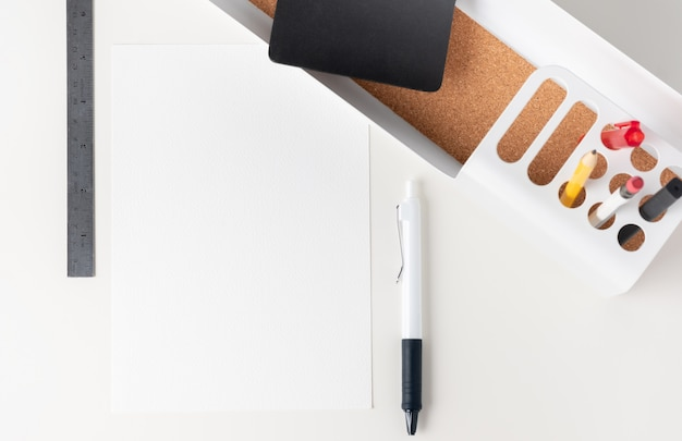 Bovenaanzicht witboek opmerking over moderne kantoorbenodigdheden op witte tafel