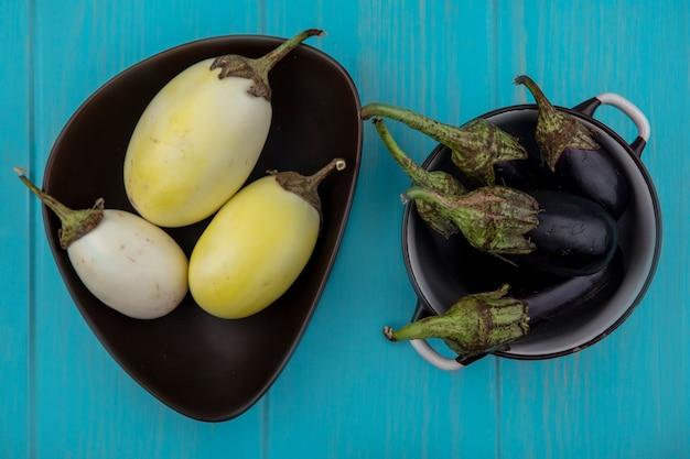 Bovenaanzicht witte aubergine in een kom met zwarte aubergine in een pan op turkooizen achtergrond