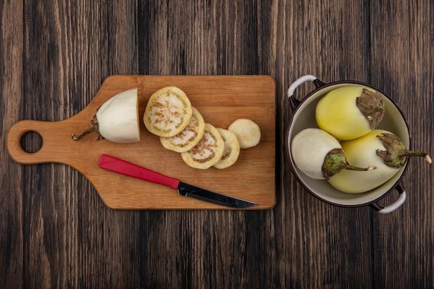 Bovenaanzicht witte aubergine plakjes met mes op snijplank en steelpan op houten achtergrond