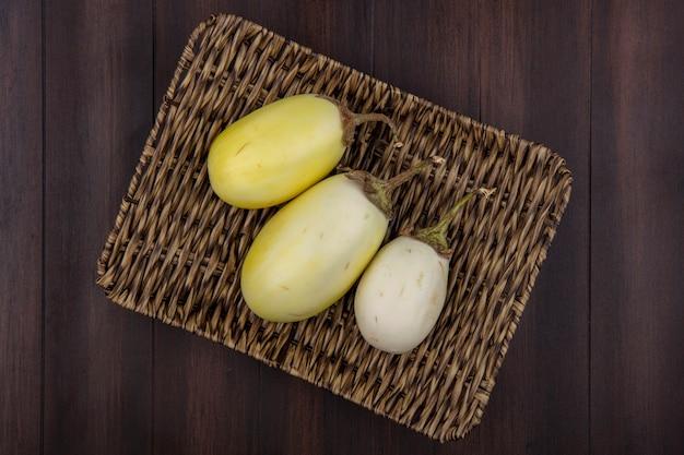 Bovenaanzicht witte aubergines op een stand op een houten achtergrond