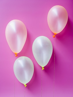 Bovenaanzicht witte ballonnen op roze achtergrond
