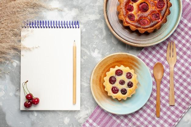 Bovenaanzicht witte blocnote met kleine cake en frambozencake op de lichte tafel fruit bessen bakken taart taart