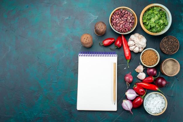 Bovenaanzicht witte blocnote samen met groenten en kruiden op de donkere foto van de de maaltijdgroente van het bureauvoedsel