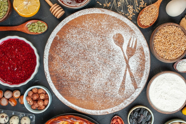 Bovenaanzicht witte bloem in vork- en lepelvorm met eieren en noten op donkere cake, zoet dessertkoekje, suikertaartthee