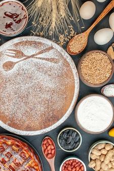 Bovenaanzicht witte bloem in vork- en lepelvorm met eieren en noten op donkere cake, zoete koekjes, suikergebak, taartthee