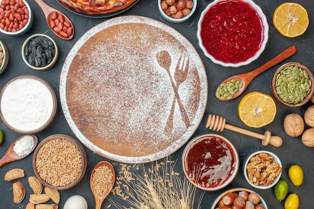 Bovenaanzicht witte bloem in vork- en lepelvorm met eieren en noten op donkere cake, zoete theedessert, biscuitgebaktaart