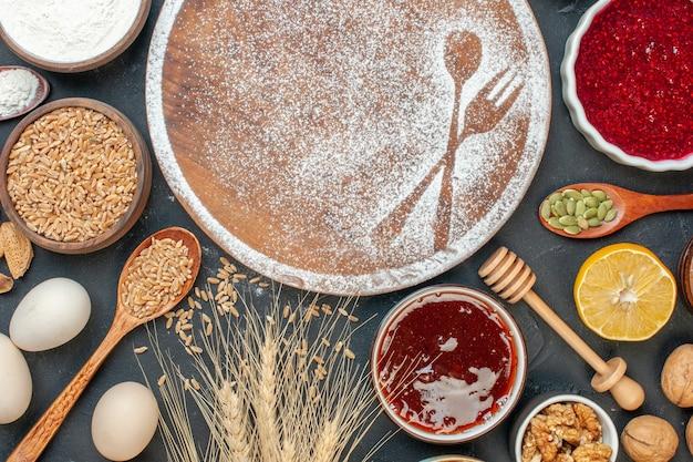 Bovenaanzicht witte bloem in vork- en lepelvorm met eieren en noten op een donkere cake, zoet dessertkoekje, suikergebak, taartthee