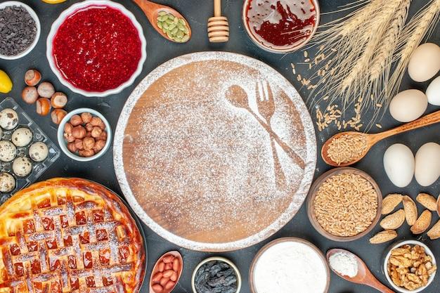 Bovenaanzicht witte bloem met noten, honing en jam op donkere cake fruit zoete taart thee dessert biscuit suiker gebak