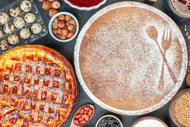 Bovenaanzicht witte bloem met noten, honing en jam op donkere cake fruit zoete thee dessert biscuit suiker gebak taart