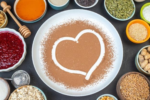Bovenaanzicht witte bloem met noten zaden granen rozijnen en gelei op de donkere achtergrond cake ontbijt eten taart stof bakken kleur koken deeg hart
