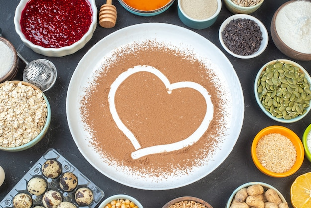 Bovenaanzicht witte bloem met noten zaden granen rozijnen en gelei op donkere achtergrond cake ontbijt eten taart stof bakken kok deeg hart