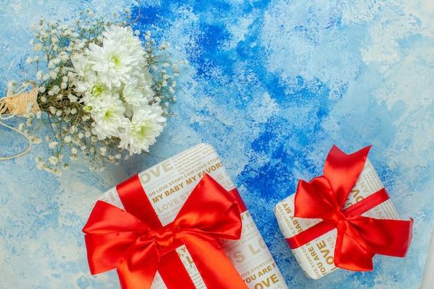 Bovenaanzicht witte bloemen geschenken in verschillende maten op blauwe achtergrond kopie plaats