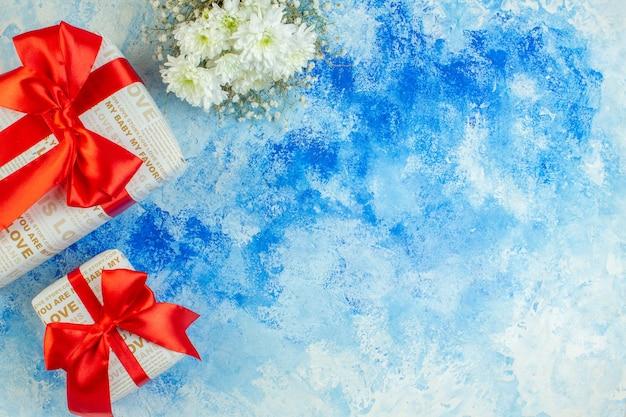 Bovenaanzicht witte bloemen geschenken op blauwe achtergrond met kopie ruimte