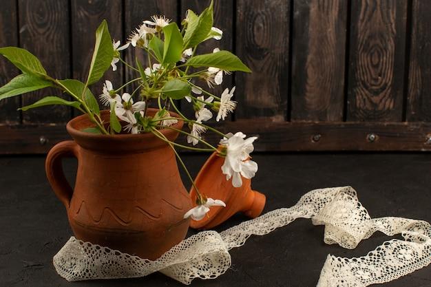Bovenaanzicht witte bloemen in bruine dip op de donkere achtergrond