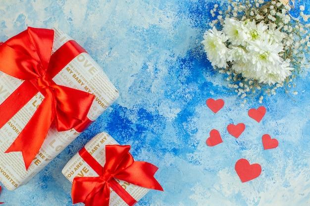 Bovenaanzicht witte bloemen kleine rode harten geschenken in verschillende maten op blauwe achtergrond