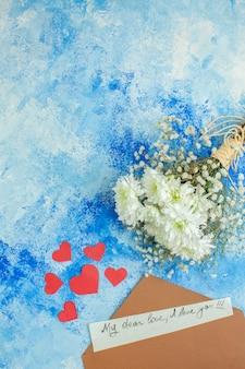 Bovenaanzicht witte bloemen liefdesbrief kleine rode harten op blauwe achtergrond