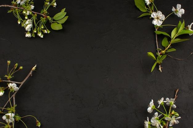 Bovenaanzicht witte bloemen op het donkere bureau