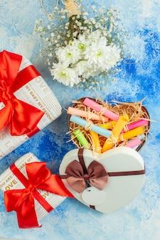 Bovenaanzicht witte bloemen opgerolde plaknotities in rood hart doos geschenken in verschillende maten op blauwe achtergrond