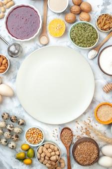 Bovenaanzicht witte bord kommen met amandelen maïszaden pinda's tarwekorrels sesamzaadjes jam eieren walnoten kwarteleitjes