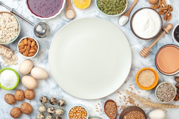 Bovenaanzicht witte bord kommen met amandelen maïszaden tarwekorrels sesamzaad eieren walnoten kwarteleitjes