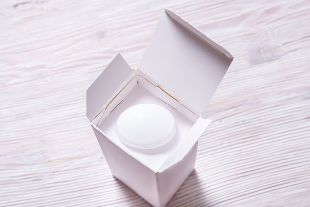 Bovenaanzicht, witte crème fles binnenkant kartonnen stuurman,