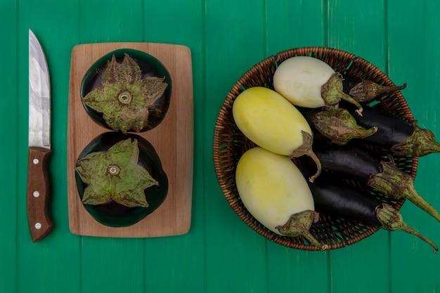 Bovenaanzicht witte en zwarte aubergine in een mand met een mes op een snijplank tegen een groene achtergrond