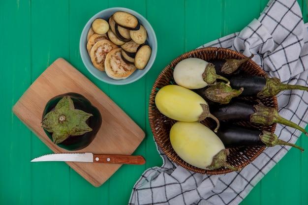 Bovenaanzicht witte en zwarte aubergine in een mand op geruite handdoeken met een mes op een snijplank op een groene achtergrond