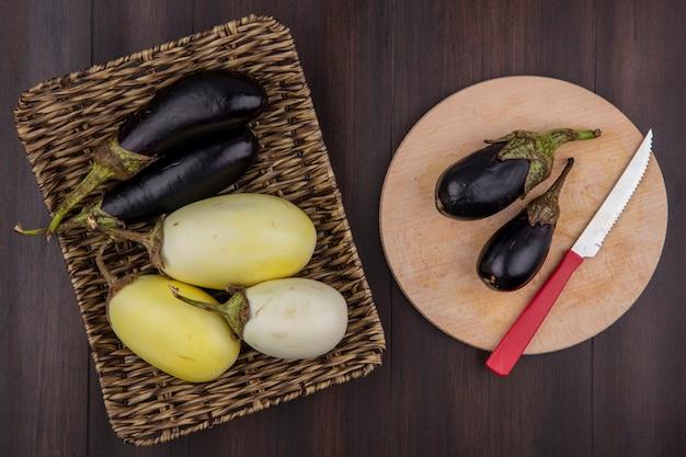 Bovenaanzicht witte en zwarte aubergine op een standaard en op een snijplank met een mes op een houten achtergrond