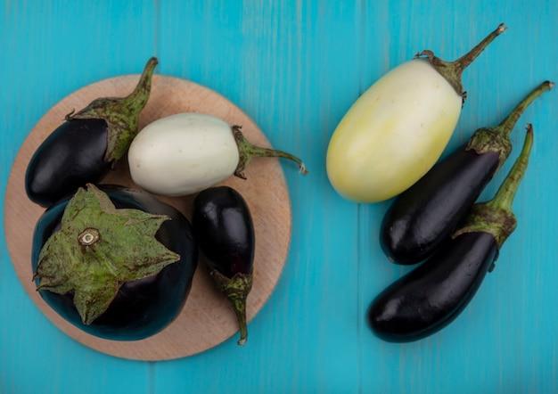 Bovenaanzicht witte en zwarte aubergines op een stand op een turkooizen achtergrond