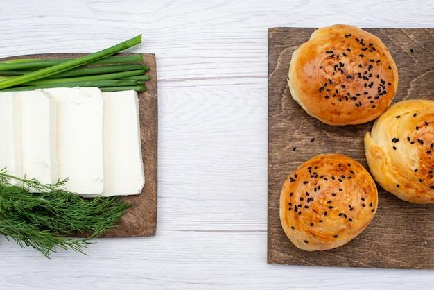 Bovenaanzicht witte kaas met greens en gebakken broodjes op het licht bureau broodje maaltijd ontbijt
