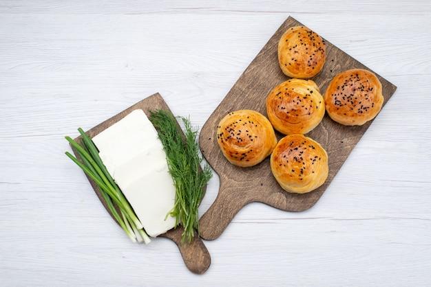 Bovenaanzicht witte kaas met vers uit de ovenbroodjes op de lichte achtergrondfoto van het voedselmaaltijdontbijt