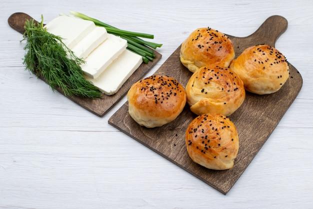 Bovenaanzicht witte kaas samen met greens en broodjes op het lichte broodje van het de maaltijdbrood van de achtergrondvoedsel