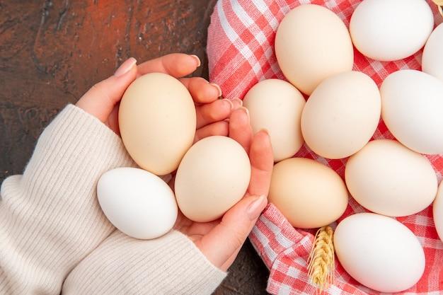 Bovenaanzicht witte kippeneieren in mand met handdoek op de donkere tafel