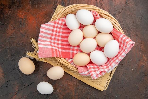 Bovenaanzicht witte kippeneieren in mand op donkere tafel