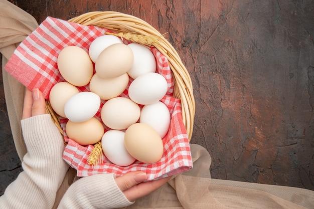 Bovenaanzicht witte kippeneieren op de donkere tafel