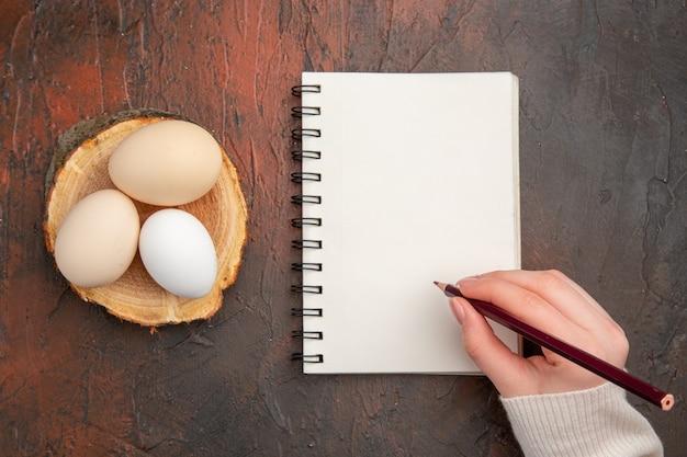 Bovenaanzicht witte kippeneieren op donker bureau