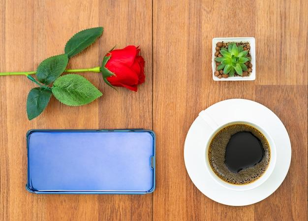 Bovenaanzicht witte kopje koffie en rode roos met mobiel op hout achtergrond valentijn concept