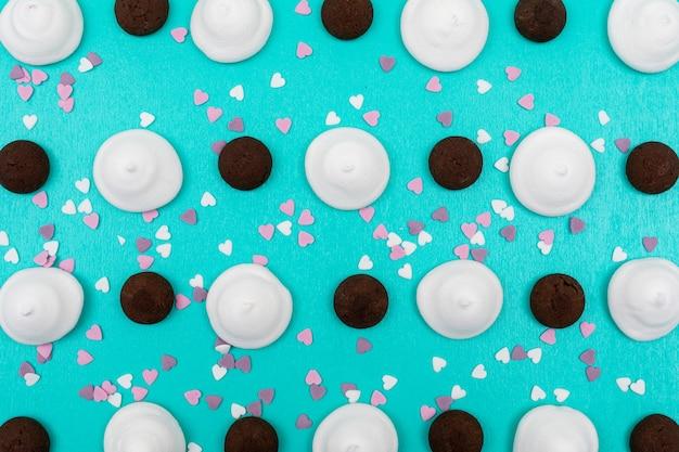 Bovenaanzicht witte marshmallows en chocoladekoekjes op blauwe ondergrond