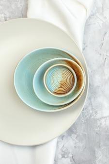 Bovenaanzicht witte plaat met borden van verschillende grootte op licht oppervlak keukenglas voedselkleur maaltijd horizontaal dames vrouwelijkheid