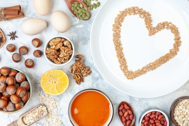 Bovenaanzicht witte plaat met gelei-eieren verschillende noten en zaden op witte deegkleur cake zoete suiker taartnoot hart