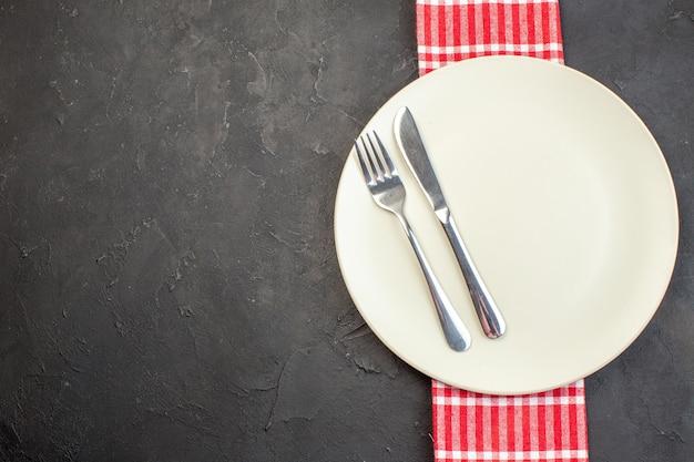 Bovenaanzicht witte plaat met mes en vork op donkere ondergrond