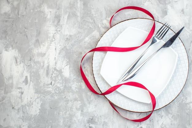 Bovenaanzicht witte plaat met vork en mes op lichte ondergrond keuken dames eten vrouwelijkheid glas maaltijd kleur horizontaal