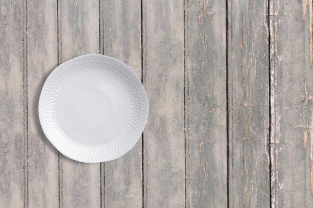 Bovenaanzicht witte plaat op donkere houten vintage tafel. kopieerruimte voor tekst toegevoegd, geschikt voor uw conceptachtergrond voor eten of drinken.