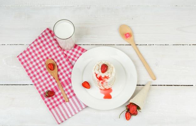 Bovenaanzicht witte rijstwafels op plaat met rood geruit tafelkleed, aardbeien, houten lepels en melk op witte houten plank oppervlak. horizontaal
