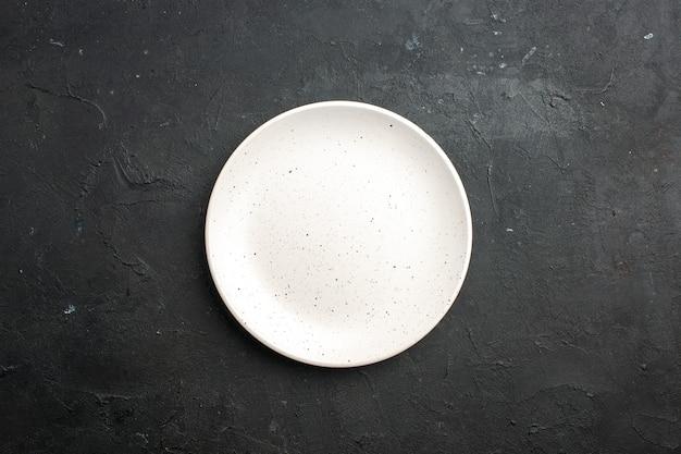 Bovenaanzicht witte saladeplaat op donkere tafel vrije ruimte