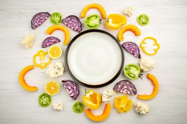 Bovenaanzicht witte schotel gesneden groenten op witte houten tafel