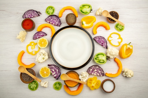 Bovenaanzicht witte schotel gesneden groenten rode kool pompoen bloemkool gele paprika kruiden in kleine kommen op witte houten tafel
