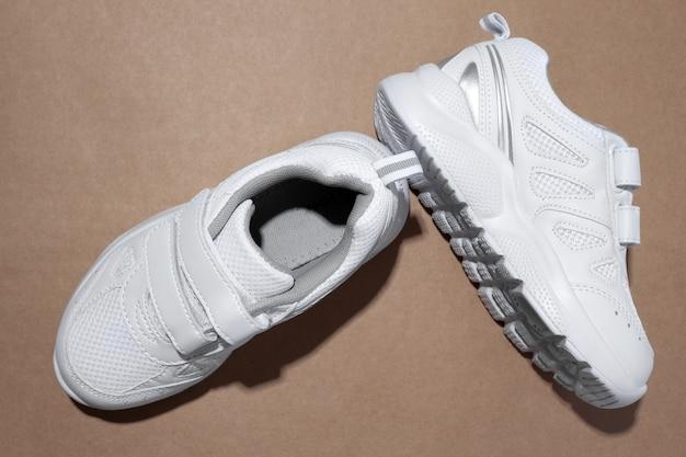 Bovenaanzicht witte unisex hardloopschoenen met klittenbandsluitingen voor gemakkelijk schoeisel met harde schaduwen isol...