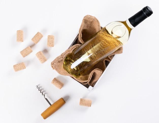 Bovenaanzicht witte wijn in fles in houten kist en linnen tas op witte horizontale