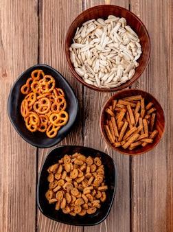 Bovenaanzicht witte zaden in kommen met bagels en paneermeel op een houten achtergrond